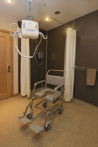 The large wet room has a hoist over the toilet and access to the middle of the room